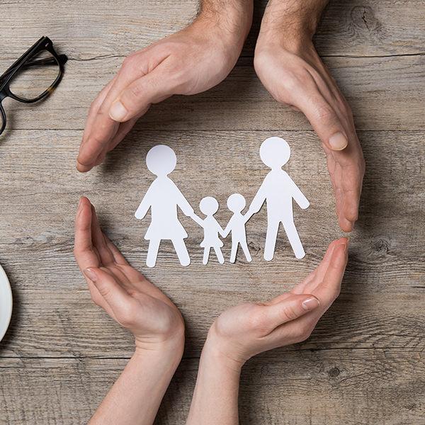 Twee paar handen omcirkelen een uitgeknipt figuur van een gezin