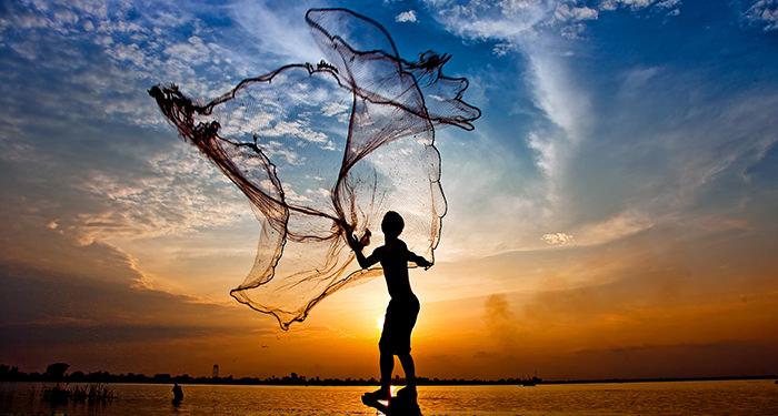 Iemand gooit een net uit over zee bij ondergaande zon