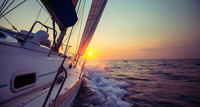 Een boot vaart over zee richting de ondergaande zon