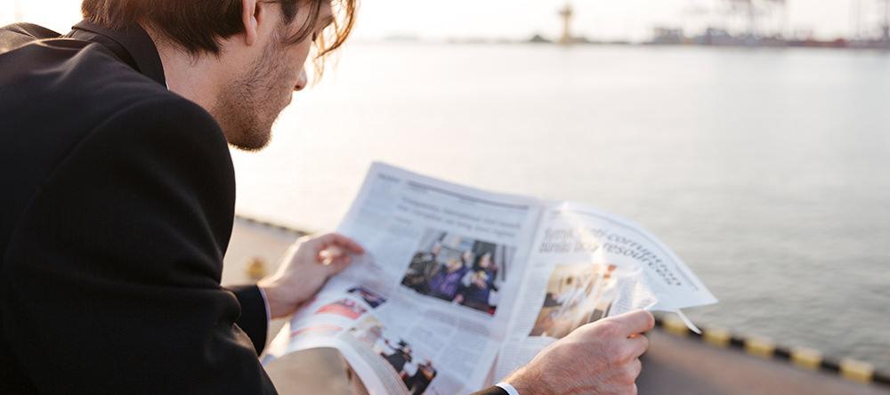 Man die buiten op een kade de krant leest