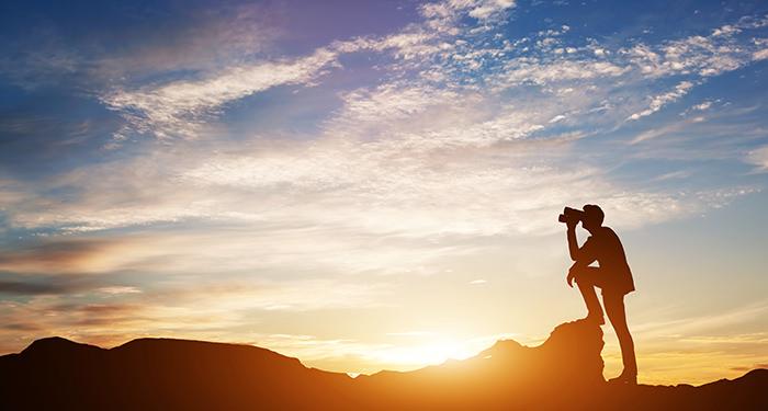 Een man kijkt met zijn verrekijker voor een ondergaande zon