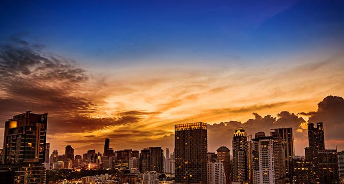 Stadslandschap met hoge gebouwen bij ondergaande zon