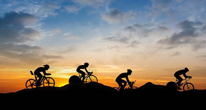 Vire wielrenners fietsen achterelkaar voor de ondergaande zon