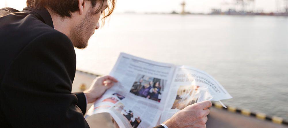 Man die buiten op een kade de krant leest - Reditus Advies nieuws