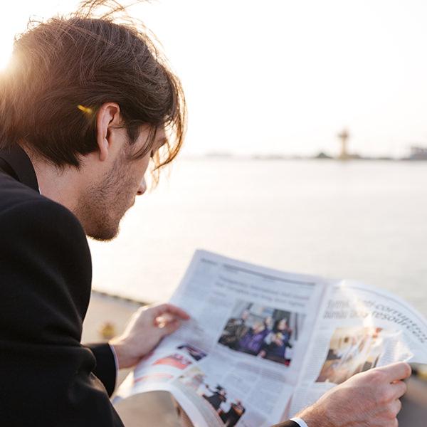 Man die buiten aan het water de krant leest
