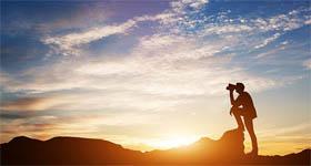 Een man kijkt met zijn verrekijker voor een ondergaande zon - Reditus Advies ondernemers en dga's