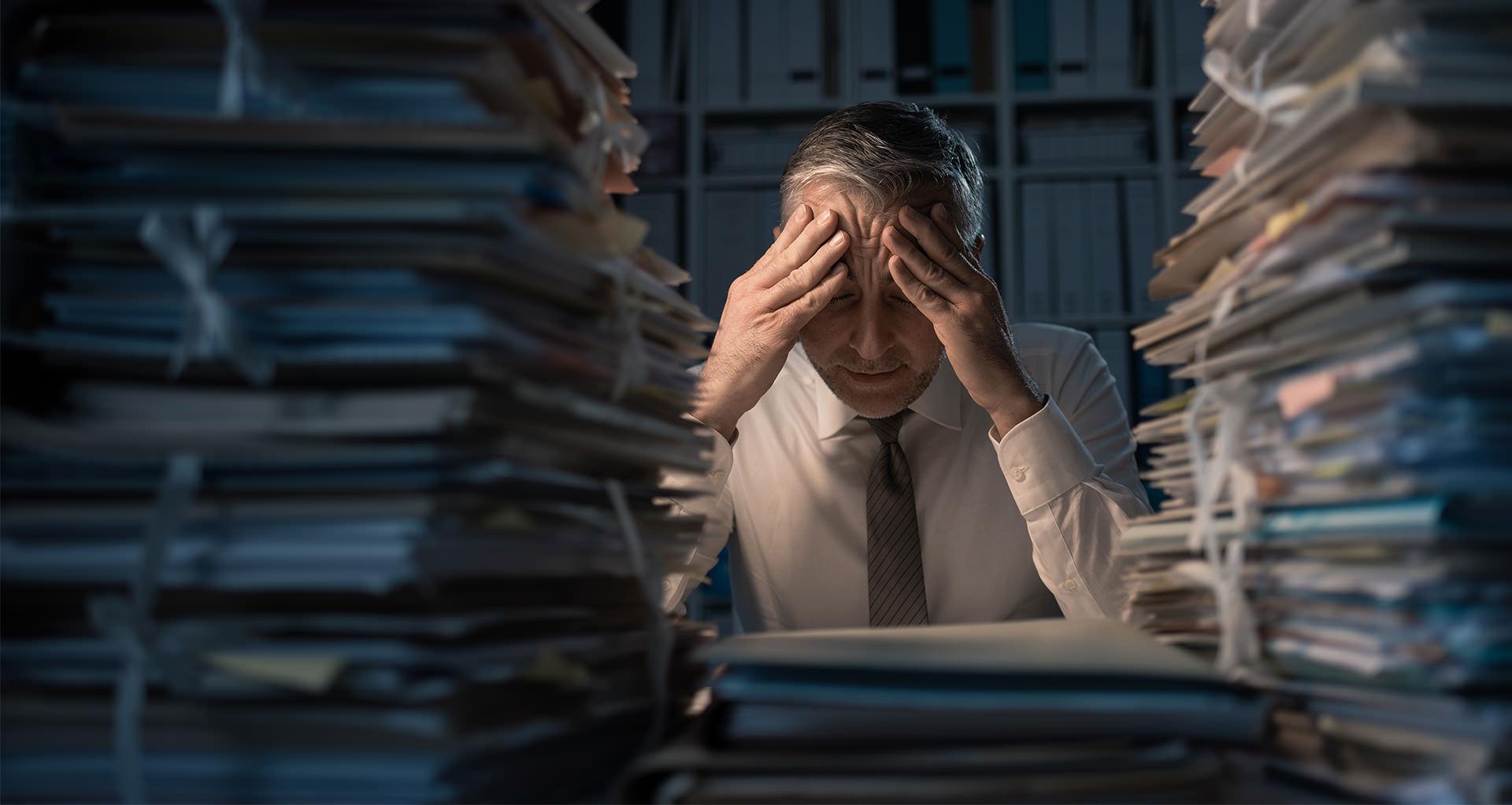 Man in stropdas steunt zijn hoofd op zijn handen tussen een berg papieren