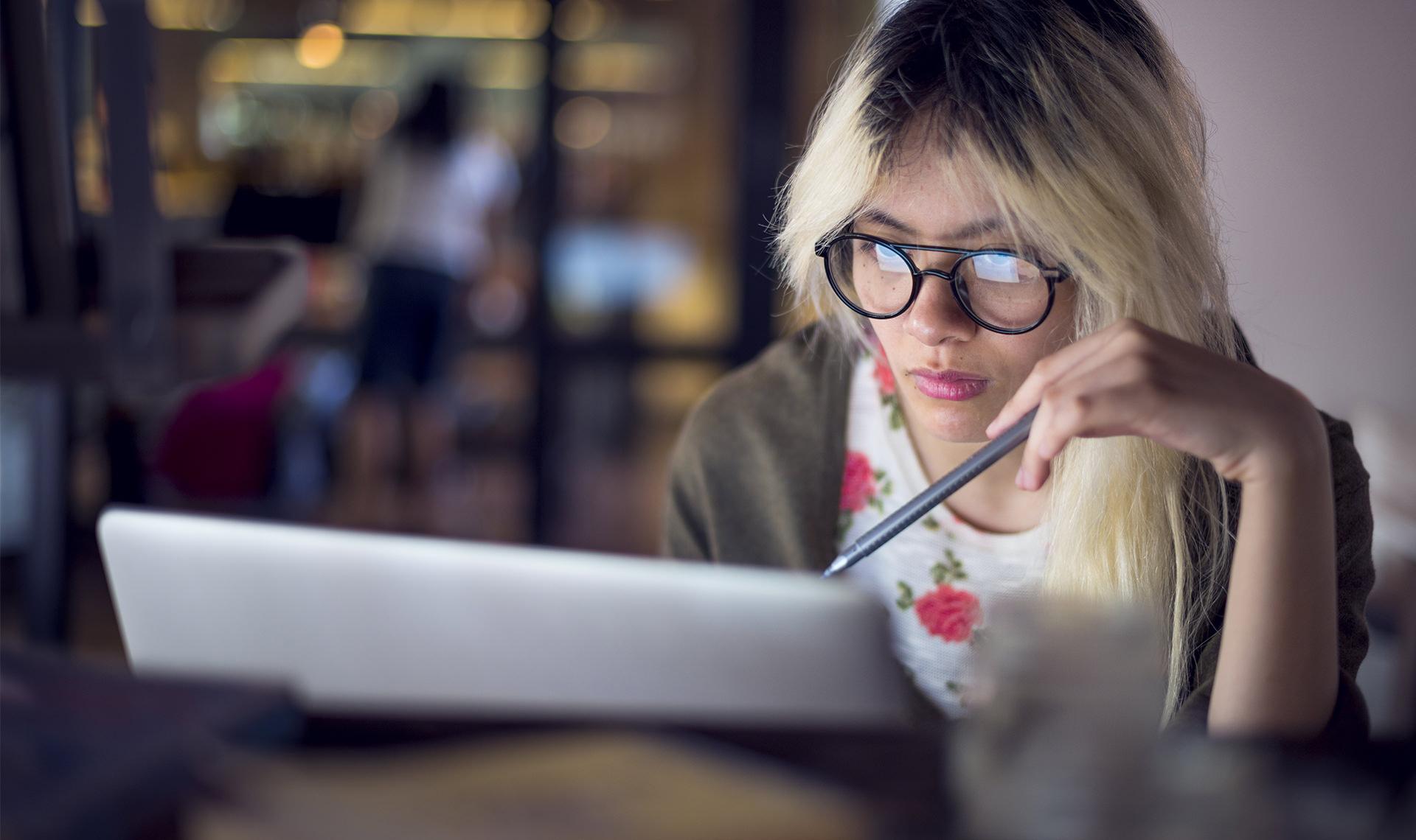 Een vrouw kijkt geconcentreerd naar haar laptopscherm